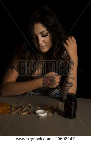 Woman With Tattoo With Drugs Spilled Looking Down