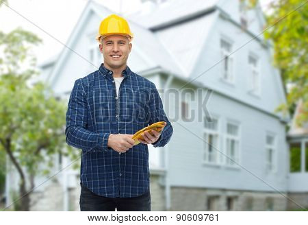 repair, building, construction and maintenance concept - smiling man in helmet with gloves over living house background