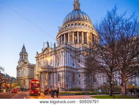 LONDON, UK - DECEMBER 19, 2014: City of London. St. Paul cathedral and red British busses in dusk.