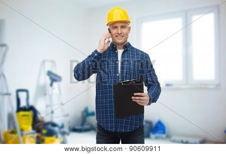 repair, building, construction and maintenance concept - smiling man or builder in helmet with clipboard calling on smartphone over storeroom background