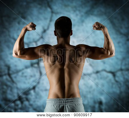 sport, fitness, bodybuilding, strength and people concept - young man or bodybuilder showing biceps over concrete wall background from back