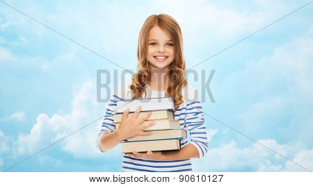 education, people, children and school concept - happy little student girl with many books over blue sky with clouds background