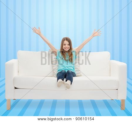 home, leisure, people and happiness concept - smiling little girl sitting on sofa with raised hands over blue striped background