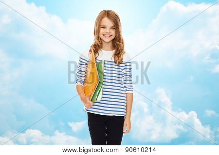 education, people, children and school concept - happy girl holding colorful folders over blue sky with clouds background