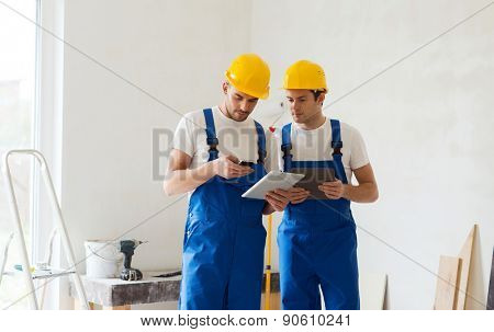 building, renovation, technology, electricity and people concept - two builders with tablet pc computer and smartphone indoors