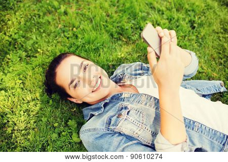lifestyle, summer vacation, technology and people concept - smiling young girl with smartphone lying on grass in park