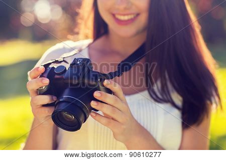 lifestyle, summer, vacation, technology and people concept - close up of young girl with photo camera outdoors