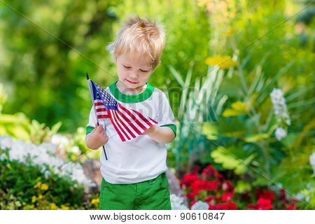 Cute Pensive Little Boy With Blond Hair Holding American Flag And Looking At It In Sunny Park