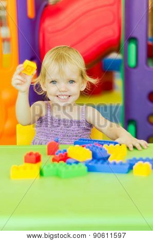 Child  Playing With Bright Plastic Construction Blocks