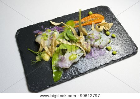 Marinated scallops served on a black slate.