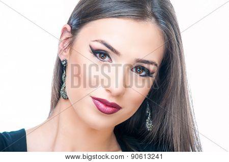 Beautiful young woman posing with earrings