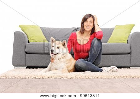 Young girl posing with a dog seated in front of a gray couch isolated on white background