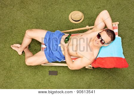 Relaxed young guy drinking beer seated on a sun lounger in his backyard, top view
