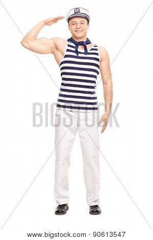 Full length portrait of a young male sailor standing straight and saluting towards the camera isolated on white background