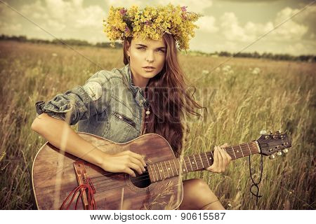 Romantic girl in a wreath of wild flowers travelling with her guitar. Summer. Hippie style.