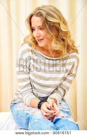 Smiling young woman resting at home, feeling harmony and happiness.