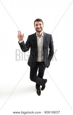 view from above of smiley businessman in formal wear waving his hand and looking at camera. isolated on white background