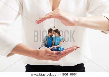 big womans hands holding small happy couple and covering them