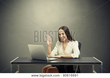 smiley businesswoman have video chat, waving her hand and looking at laptop over dark background