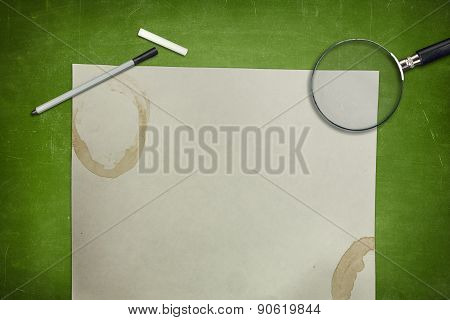 Green blackboard with empty paper sheet and magnifying glass