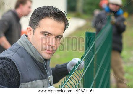 Gardening team putting up a garden fence