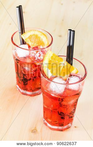 Two Glasses Of Spritz Aperitif Aperol Cocktail With Orange Slices And Ice Cubes On Wood Table