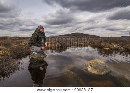 Man Traveler On Marshland Against The Backdrop Of Rain Clouds.