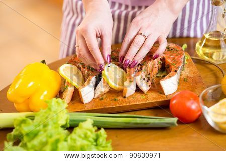 Female hands cooking trout fish in domestic kitchen