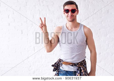 Portrait of funny smiling hipster man in red heart shaped glasses looking at camera showing peace v-