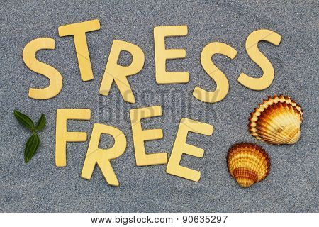 Stress free written with wooden letters on blue sand with seashells