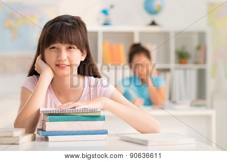 Schoolgirl with stack of books