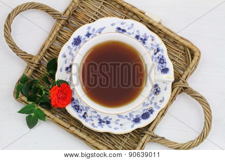 Tea in vintage porcelain cup on wicker tray and red wild rose