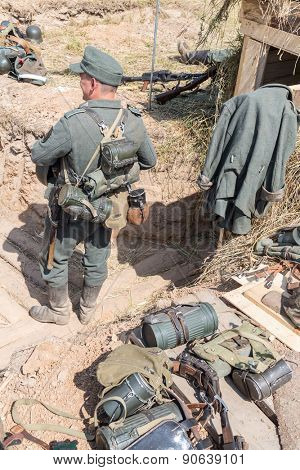 NELIDOVO, RUSSIA- JULY 12, 2014: Battlefield 2014: Nazi soldier standing back near scattered ammunition