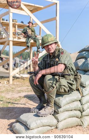 NELIDOVO, RUSSIA- JULY 12, 2014: Battlefield 2014: GI shows a gesture of peace sitting on bags