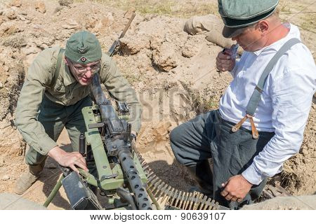 NELIDOVO, RUSSIA- JULY 12, 2014: Battlefield 2014: two Nazi soldier with a machine gun in a trench