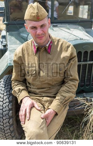 NELIDOVO, RUSSIA- JULY 12, 2014: Battlefield 2014: Soviet soldier sitting on the hood of a truck