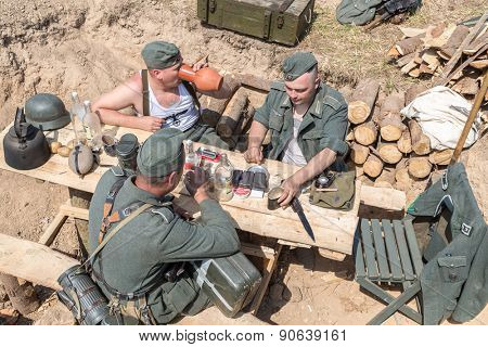 NELIDOVO, RUSSIA- JULY 12, 2014: Battlefield 2014: three Nazi soldiers dine at a table in the trenches