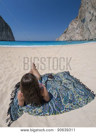 Woman relaxing on the famous Shipwreck Navagio beach in Zakynthos Greece