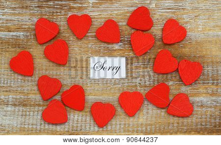 Sorry card with little red hearts scattered on rustic wooden surface
