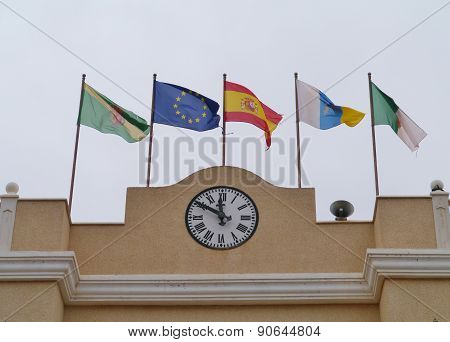 A clock and flags on a building