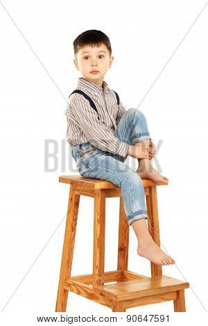 Portrait Of A Funny Little Boy Sitting Barefoot On A High Stool