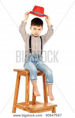 Portrait Of A Funny Little Boy Sitting On A High Stool In A Red Hat