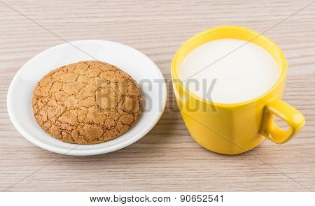 One Cookie In Saucer And Yellow Cup Of Milk