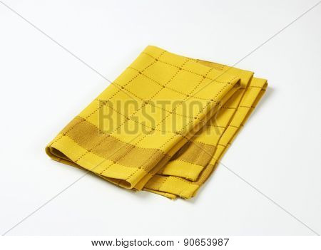 yellow and brown checkered dishtowel on white background