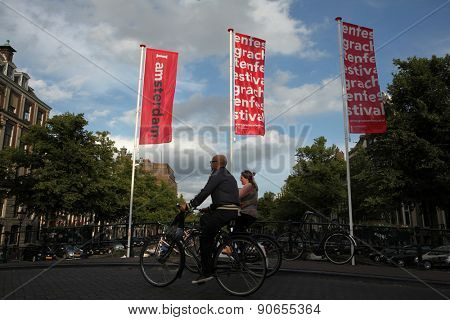 AMSTERDAM, NETHERLANDS - AUGUST 9, 2012: Two cyclists pass over the bridge decorated with banners with an official brand of the city in Amsterdam, Netherlands.