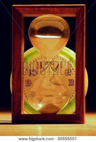 Sandglass in front of clocks