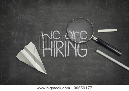 We are hiring concept on black blackboard with magnifying glass