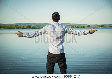 Young man outdoor with arms spread open enjoying freedom