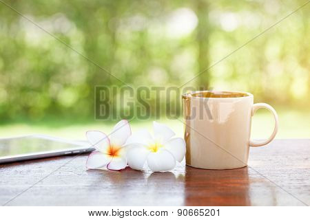 Coffee With Flowers And Tablet On Wooden Table
