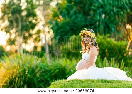 Young smiling pregnant woman in white dress with flowers in her hair